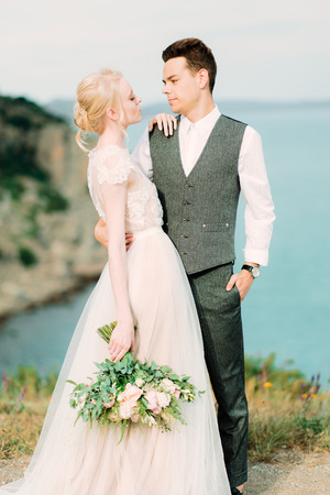 Beautiful bride and groom hug each other tender standing on the golden hill near sea