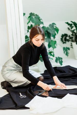 Beautiful seamstress, cut black fabric on the studio floor,draws on fabric Imagens