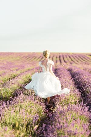 Wonderful portrait of girl in light dress in lavender field on golden sunset 版權商用圖片