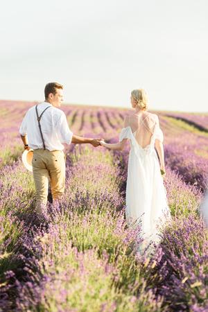Beautiful portrait of bride and groom hug each other tender on sunset in lavander field