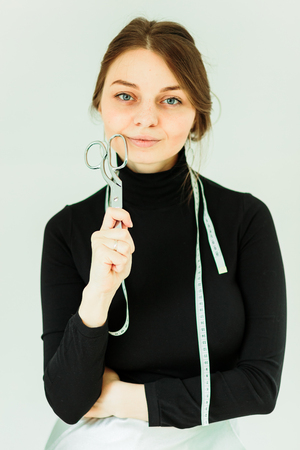 smiling seamstress holding scissors and looking at camera