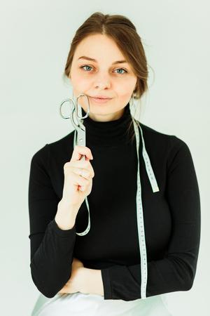 sorridente sarta tenendo le forbici e guardando la fotocamera