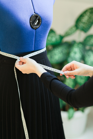 sewing blue mannequin with main marks for removing of measures standing on a white studio and green flower