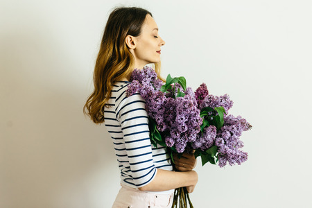 Pretty girl in a striped t-shirt with a bouquet of lilacs on a white background Reklamní fotografie - 122685880
