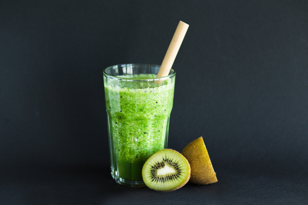 Healthy green smoothie with bamboo tube in a glass cup on a black background Stock fotó