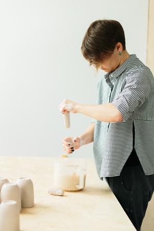woman ceramist, sculpts clay product in the Studio. handmade ceramic cup Banco de Imagens