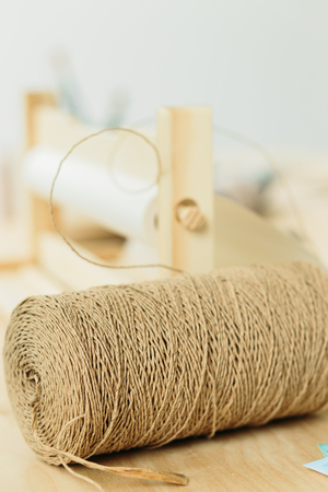 reel with string for gift wrapping on wooden table in a studio