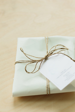 gift wrapped in white paper , tied with a lace