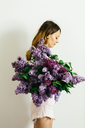 Beautiful women with a purple bouquet of lilac on a white background 版權商用圖片