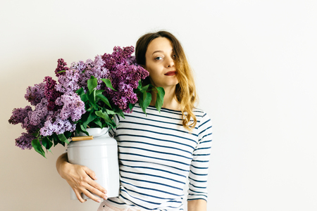 Beautiful women with a purple bouquet of lilac on a white background Reklamní fotografie - 122886098