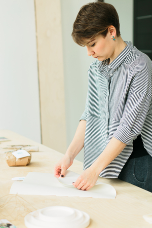 girl packs a gift on a wooden table in a studio 版權商用圖片
