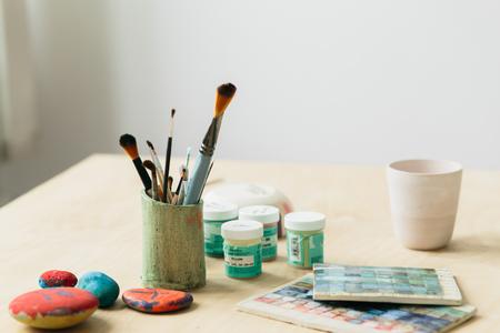Potter holds the color palette glazes for coating ceramic products on wood table Reklamní fotografie