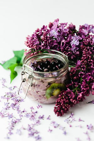 healthy smoothie breakfast in a glass jar with lilac flowers on white background Stok Fotoğraf