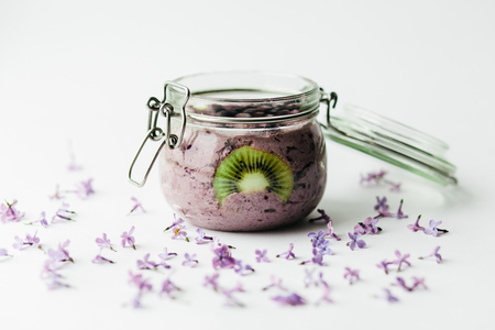 healthy smoothie breakfast in a glass jar with lilac flowers on white background Stock Photo