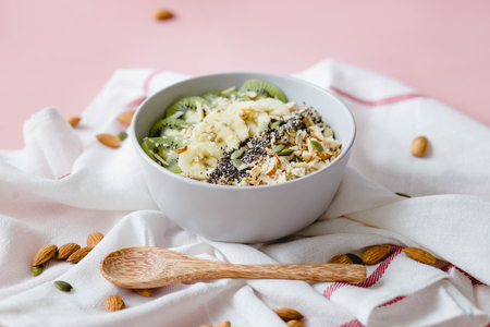 healthy Breakfast of oatmeal with kiwi, banana and chia seed on a white napkin, on pink background
