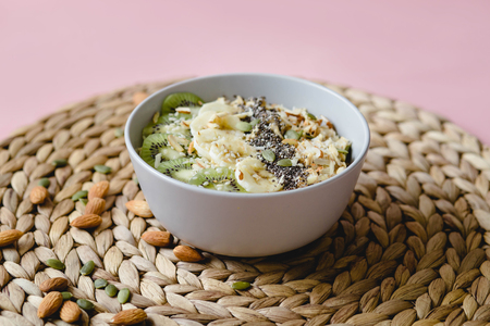 healthy Breakfast of oatmeal with kiwi, banana and chia seed on a wicker napkin, on pink background