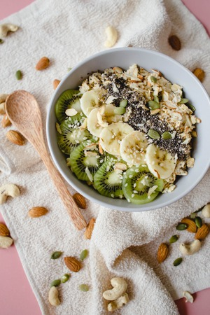 healthy Breakfast of oatmeal with kiwi, banana and chia seed on a white napkin, on pink background Stock Photo