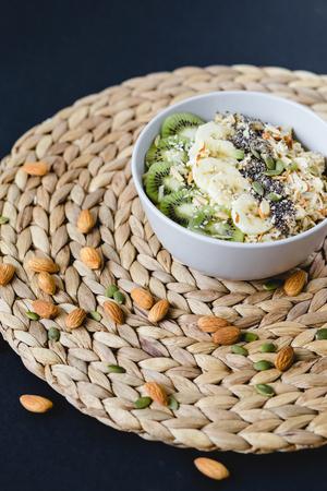 healthy Breakfast of oatmeal with kiwi, banana and chia seed on a wicker napkin Stock Photo