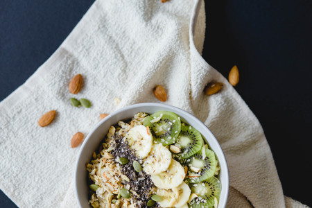 healthy Breakfast of oatmeal with kiwi, banana and chia seed on a white napkin, on black background