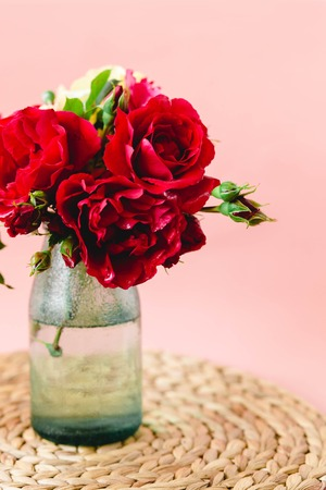 Coloful roses in vase on a nature wicker napkin on pink background