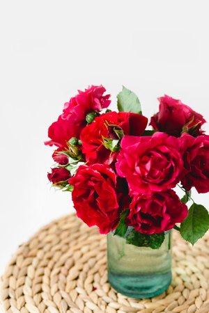 Coloful roses in vase on a nature wicker napkin on white background 版權商用圖片
