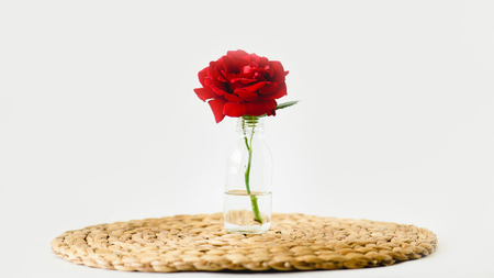 Red roses in glass vases on a nature wicker napkin on white background 版權商用圖片