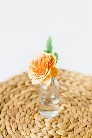 Orange rose in glass vase on a nature wicker napkin on white background