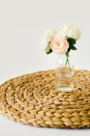 Beautiful roses in glass vase on a nature wicker napkin on white background