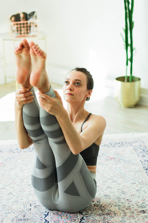 Young attractive smiling woman practicing yoga in a large, bright room