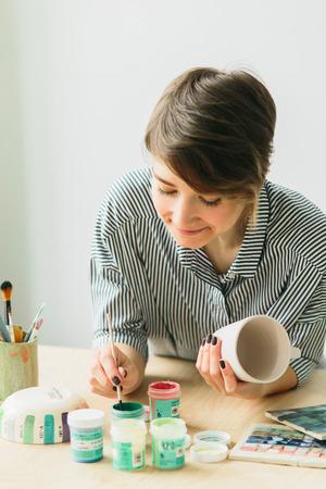 de aardewerkvrouw houdt een mok in handen om het ornament te schilderen, handgemaakt keramiek Stockfoto