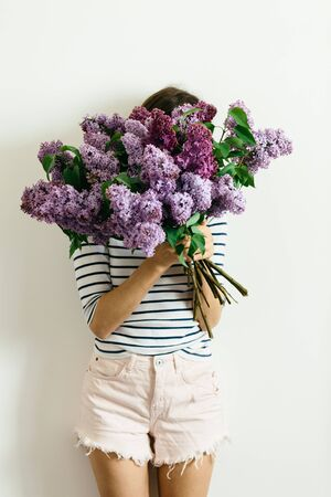 Pretty girl in a striped t-shirt with a bouquet of lilacs on a white background