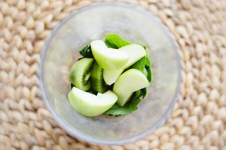 spinach, kiwi and green Apple in a glass on a wicker table, nature background