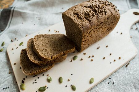 Freshly baked sliced bread on a wooden Board on dark grey fabric with seed