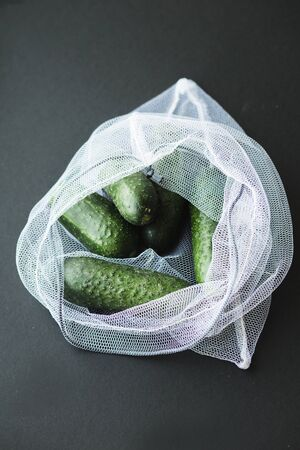 Reusable eco-friendly bag full of fresh seasonal cucumber. Caring for the environment and the rejection of plastic concept