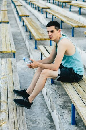 A young man sitting on a bench and tying his shoelaces in the fresh air in new York. He's wearing a t-shirt and gym shorts.