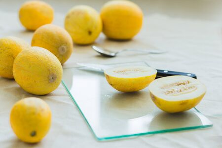 Melon berries and sliced juicy melon halves on the kitchen table . glass eco Board with knife Reklamní fotografie