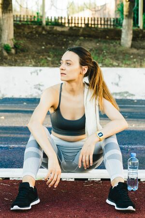 Young woman with a bottle of water after Jogging outdoors in Singapore. She is wearing grey top and a light sports leggings