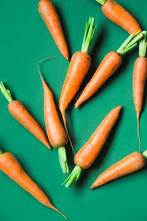 A few fresh carrots on green background. Rustic style. Farming.