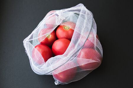 Reusable eco-friendly bag full of fresh seasonal tomatoes. Caring for the environment and the rejection of plastic concept