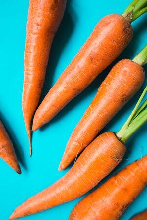 A few fresh carrots on blue background. Rustic style. Farming. Reklamní fotografie