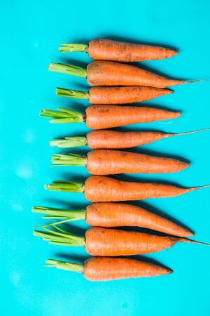 several fresh carrots in a row on a blue background.. Rustic style. Farming. Reklamní fotografie