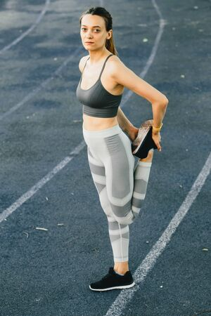 Young woman doing outdoor exercise in new York. She is wearing a grey top and light sport leggings