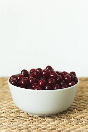 A plate full of fresh cherries on a natural wicker napkin. season berries