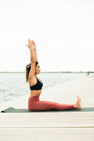 Asian young girl doing yoga outdoors on the pier by the lake. shes wearing a black top and red leggings.