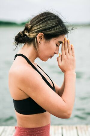 Asian young girl meditating outdoors on the pier by the lake. shes wearing a black top and red leggings. Reklamní fotografie