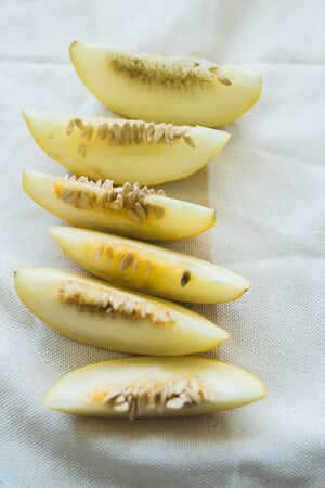 A group of brightly lit melon slices. seasonal summer fruits