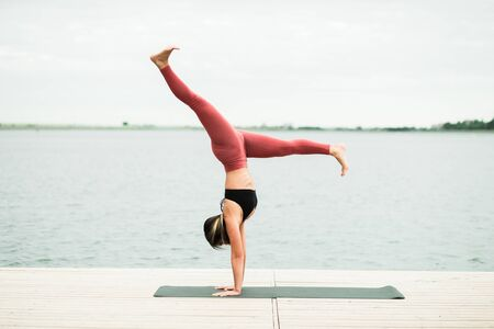 Asian young girl doing yoga outdoors on the pier by the lake. she's wearing a black top and red leggings.
