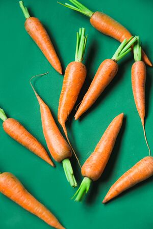 A few fresh carrots on green background. Rustic style. Farming.