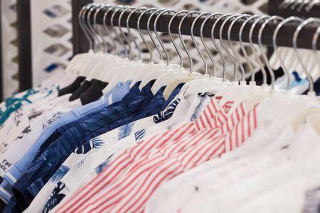 L'appendiabiti è pieno di camicie in tessuto colorate. Camicie pulite appese su rack in lavanderia, primo piano