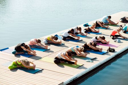 A big group of people attending yoga classes on a pontoon near the lake.
